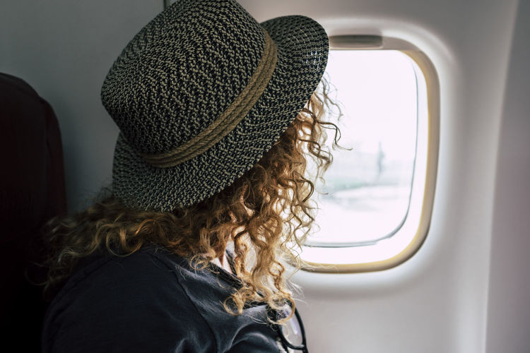 Side view of woman looking through window while sitting in airplane