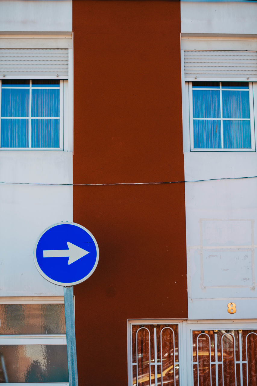 building exterior, architecture, built structure, window, communication, road sign, outdoors, blue, day, no people, guidance, low angle view, close-up