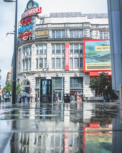 Manchester Manchester UK Puddles Reflection Architecture Building Building Exterior Built Structure City Communication Day Glass - Material Incidental People Outdoors Printworks Manchester Rain Rainy Season Reflection Sign Street Text Transportation Travel Destinations Water Window