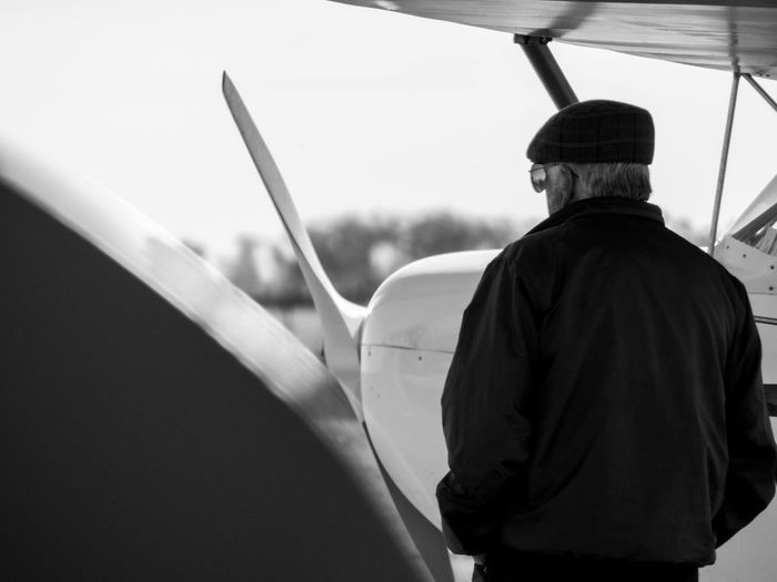 Rear view of man standing by airplane