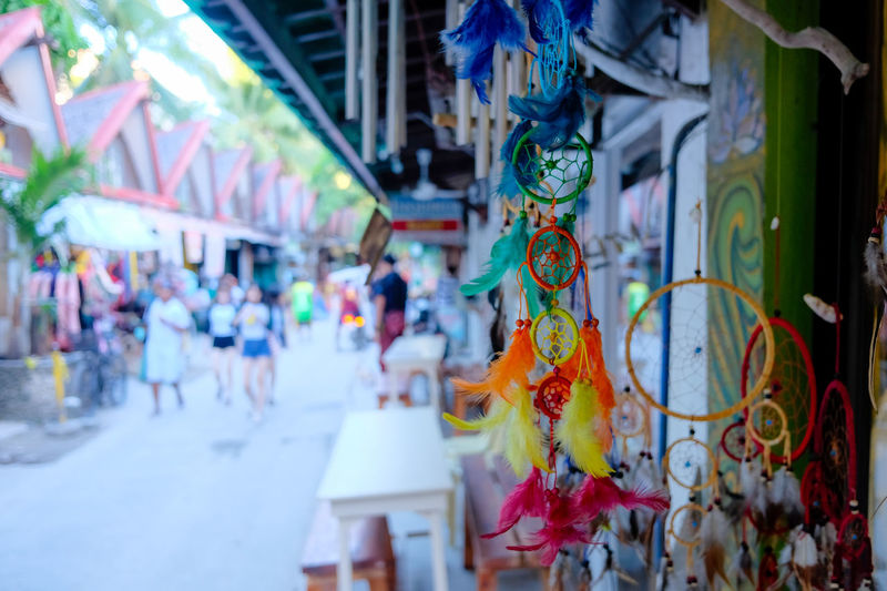 Architecture Art And Craft Building Exterior Built Structure City Creativity Day Decoration Focus On Foreground For Sale Hanging Incidental People Multi Colored Outdoors Real People Retail  Selective Focus Store Street