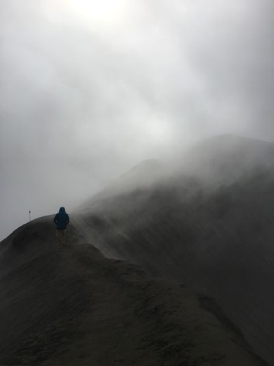Rear View Of Man Walking On Mountain Against Sky During Foggy Weather