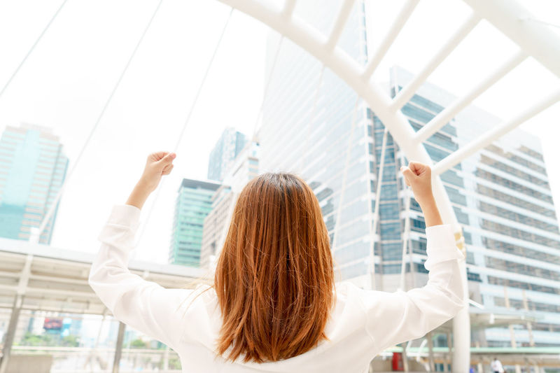 Businesswoman clenching fists against modern buildings