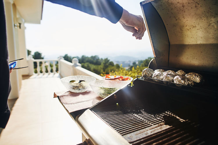 Cropped image of hand preparing food in balcony during sunny day