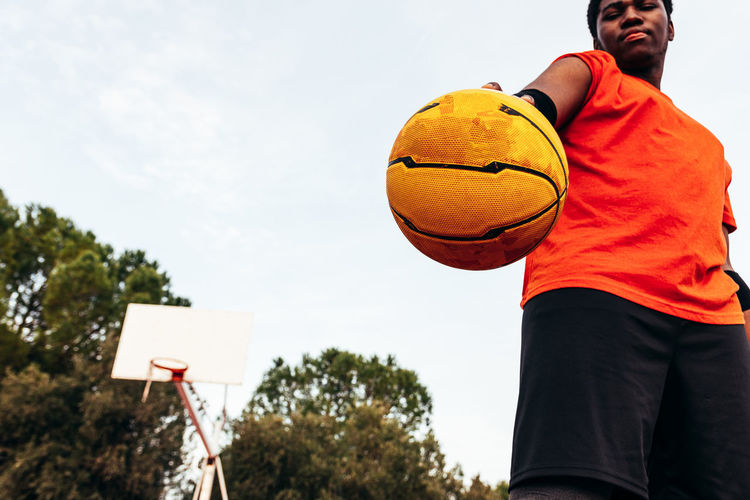 Low angle view of man holding ball against sky