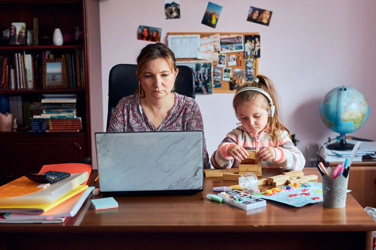 Mother working in laptop while daughter playing with cube shape on table at home