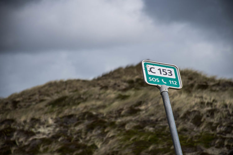 Low angle view of road sign with numbers and alphabets against sky