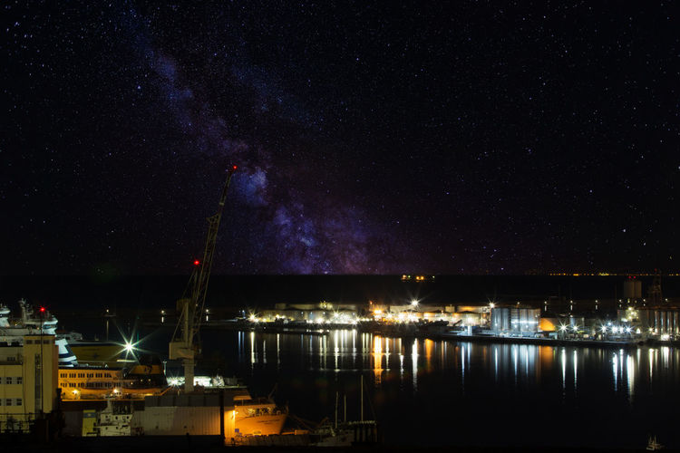 Illuminated harbor against sky at night