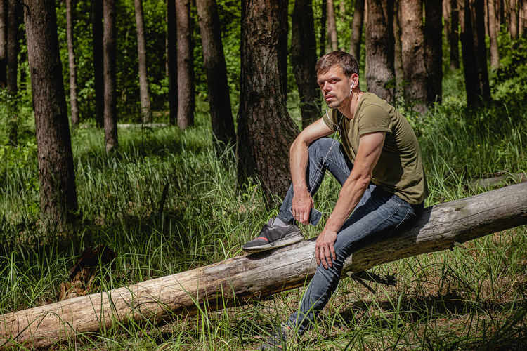 A man in a forest sits leaning against a tree, with headphones in her ears listening to music.
