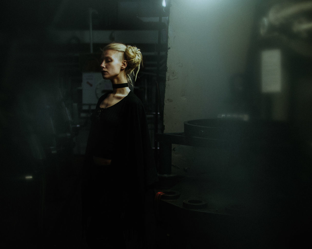 SIDE VIEW OF YOUNG WOMAN STANDING IN DARK