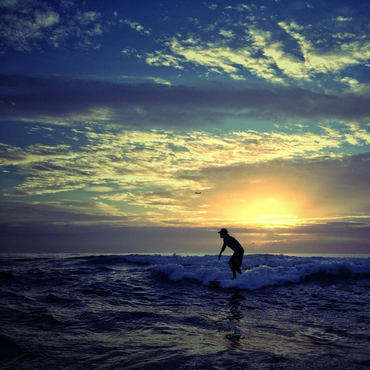 Side view of a silhouette person surfing in the sea