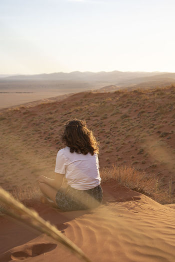 Rear view of woman sitting on sand