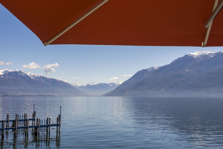 Umbrella over Alpine Lake Maggiore with Mountain in a Sunny day in Ticino, Switzerland. Pier Tranquility Blue Built Structure Color Full Frame Idyllic Lake Lake Maggiore Landscape Mountain Mountain Peak No People Outdoors Protection Red Color Scenics Sky Swiss Alps Tranquil Scene Umbrella Water Watersurface