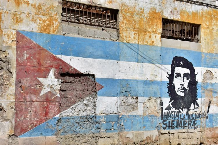 Che Guevara on a Cuban flag. Been There. Che Guevara Mural Cuba Cuban Revolution Cuban Flag Havana Havana, Cuba Architecture Building Exterior Built Structure Che Guevara Che Guevara Painting Close-up Day Faded Color Flag Graffiti Multi Colored No People Outdoors Street Art Weathered Connected By Travel