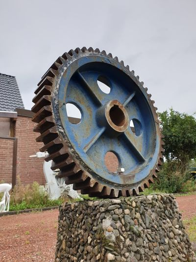 Low angle view of rusty wheel against sky