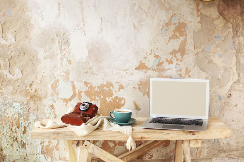 Coffee cup on table against wall at home