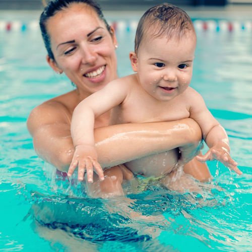 Close-Up Of Mother Holding Toddler Son In Pool