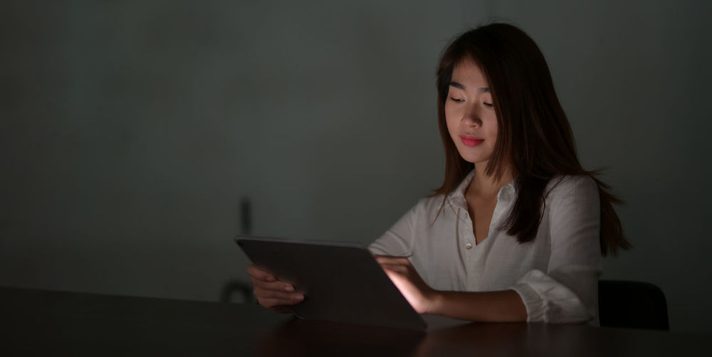 Businesswoman using digital tablet while sitting on table