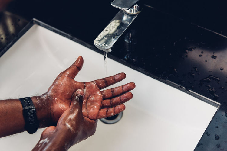 Close-up of man hand with faucet in water