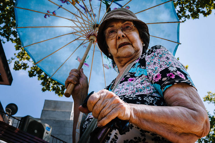 Low angle view of woman holding umbrella against sky