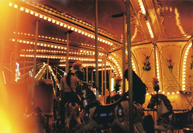 People in amusement park ride at night