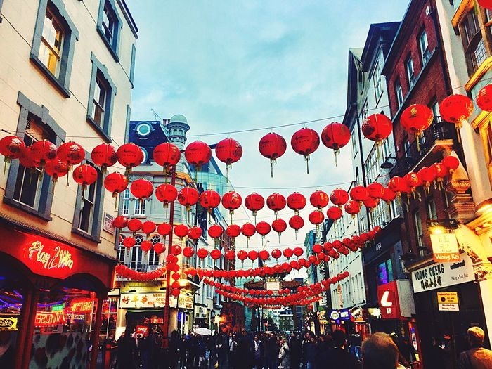 Low angle view of lanterns hanging in city against sky
