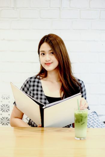 Portrait of beautiful woman sitting on table against wall