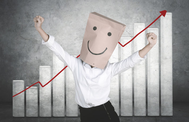 Businesswoman wearing paper bag with anthropomorphic face against graph