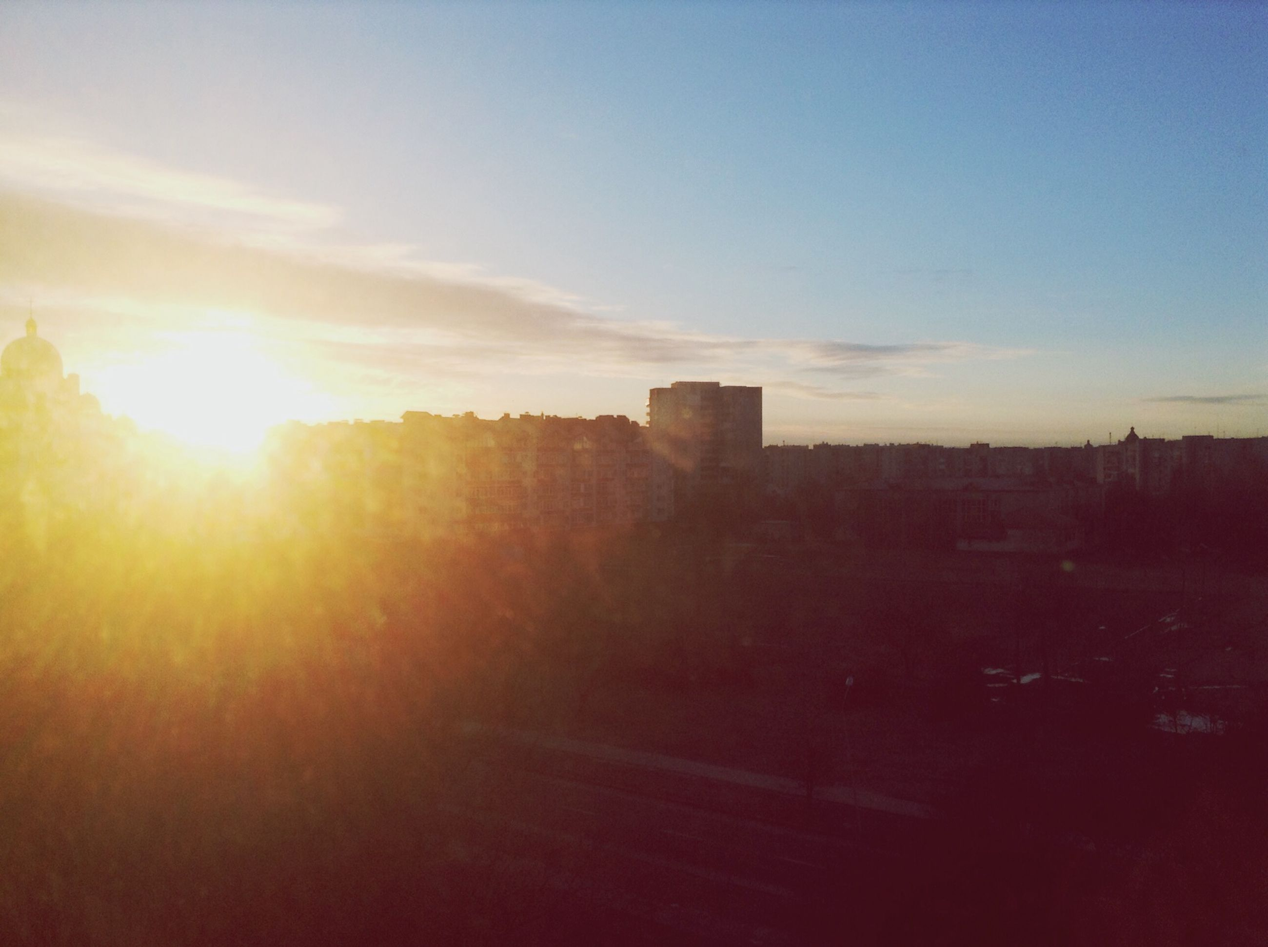 sunset, building exterior, sun, architecture, built structure, sunlight, sunbeam, sky, city, lens flare, cityscape, silhouette, outdoors, residential structure, orange color, residential building, no people, nature, building, scenics