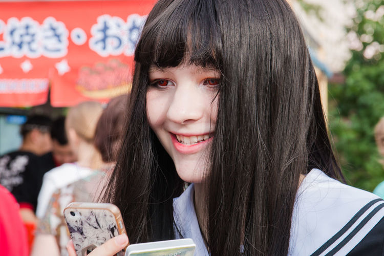 Cosplay Beautiful Woman Communication Day Focus On Foreground Hair Hairstyle Happiness Headshot Holding Leisure Activity Lifestyles Long Hair One Person Portrait Real People Smiling Technology Wireless Technology Women Young Adult