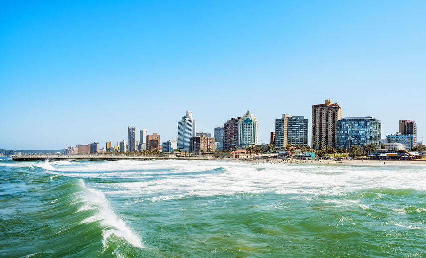 Panorama photo of Durban South Afrika. Big waves crossing the scene An Eye For Travel Bay Of Plenty Region Durban Architecture Beach Blue Building Exterior Built Structure City Cityscape Clear Sky Durban Skyline Nature Outdoors Power In Nature Sea Shore Skyline Skyscraper Surf Tower Travel Destinations Urban Skyline Water Waterfront