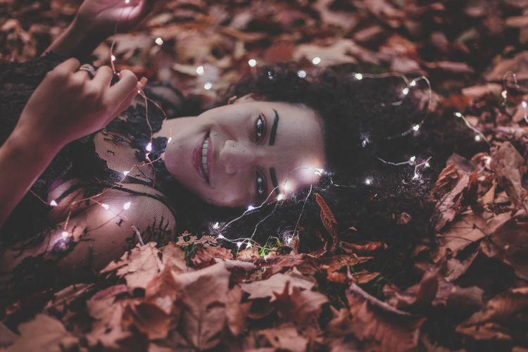 Close-Up Portrait Of Beautiful Woman Holding Illuminated Lights