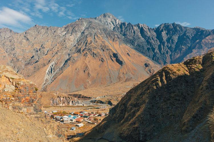 Stepantsminda, kazbegi, goergia. cityscape of big rural town with mountain range of mount kazbak.