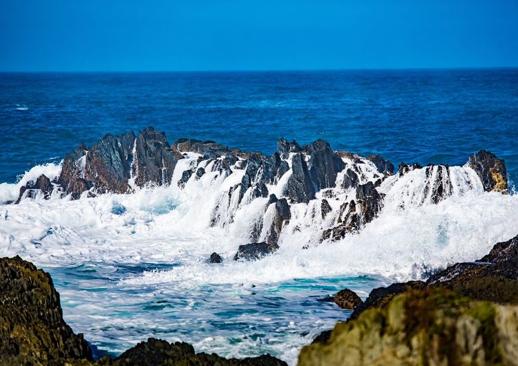 Scenic view of rocks in sea against blue sky