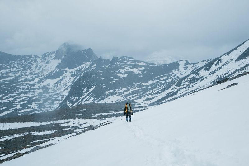 Person climbing on snowcapped mountain against sky