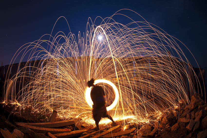 Light graffiti or light painting spinning steel wool with a person silhoutte (using burnt steel wool and slow shutter photography) Bulb Mode Fire Firework Display Fireworks Heat - Temperature Light Graffiti Light Motion Light Painting Long Exposure Motion Night Nightphotography One Man Only One Person Outdoors Performance Performing Arts Event Silhoutte Sky Slow Shutter Spinning Steel Structure  Wire Wool