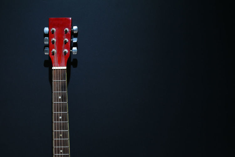 Close-Up Of Acoustic Guitar Against Black Background