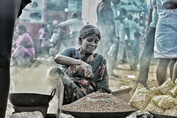 Full length of woman selling food for living at a busy marketplace