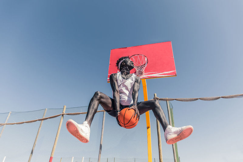 Low angle view of basketball player jumping against clear sky