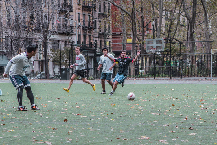 People playing soccer ball in park