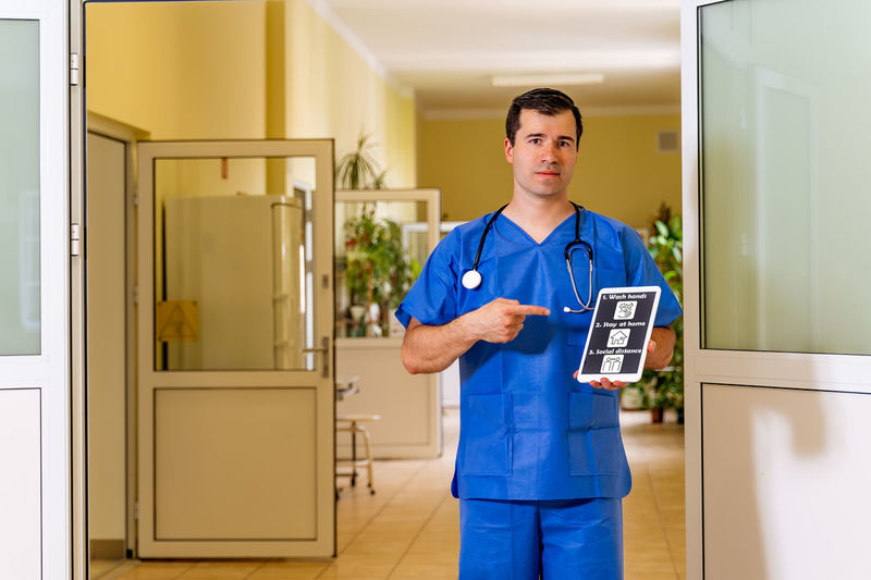 Full length of young man standing in front of door