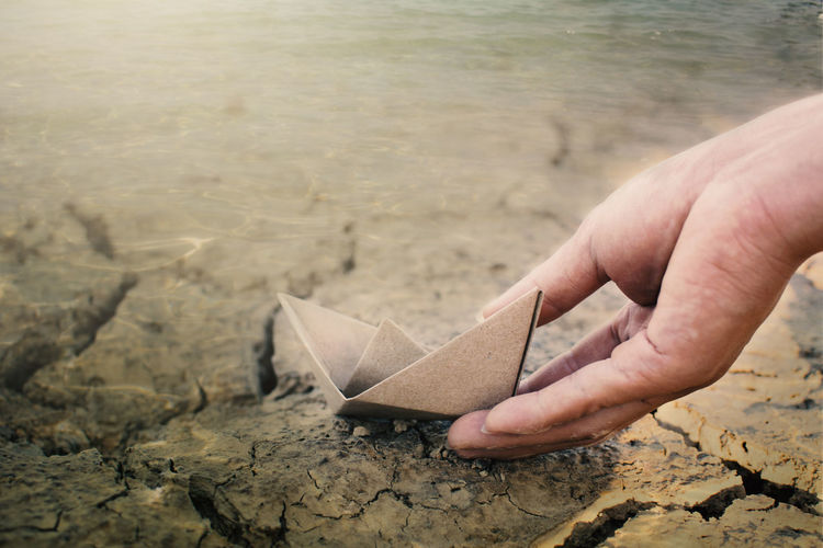Close-up of hand with paper boat at beach