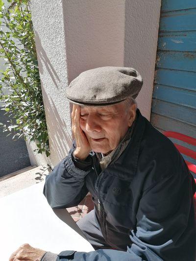 Senior man wearing hat sitting outdoors