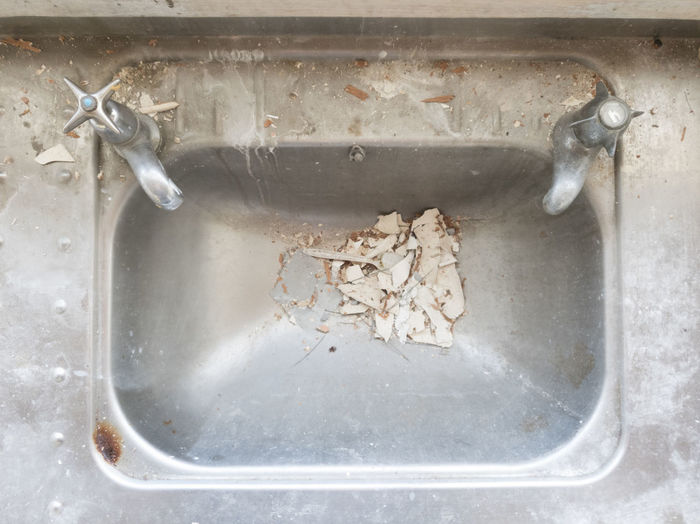 High angle view of old faucet in water