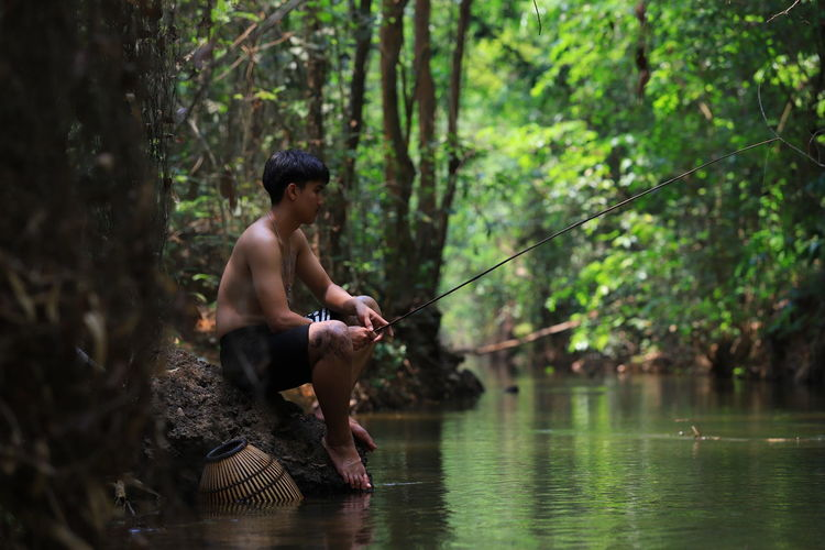 Full length of shirtless man fishing while sitting by lake in forest