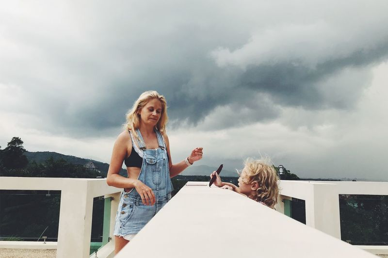 Mother And Daughter On Terrace Against Sky