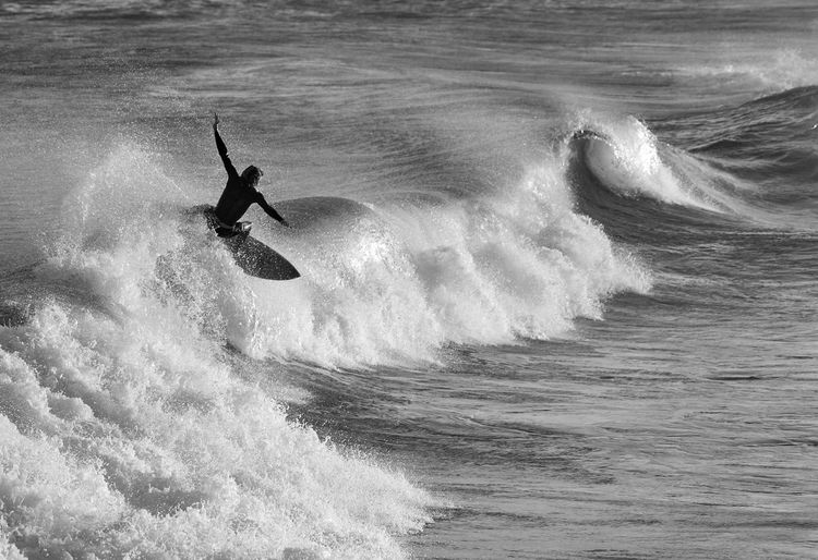 Person with arms outstretched surfing in sea