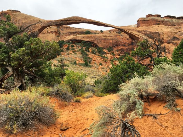 Natural rock arch against cloudy sky