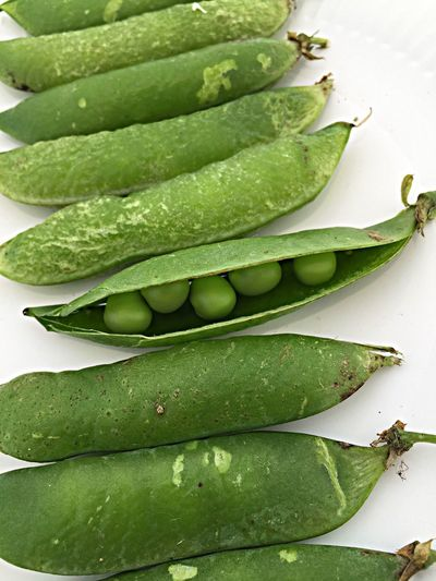 High angle view of green peas on white background