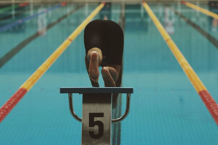 Rear View Of Swimmer Jumping In Pool